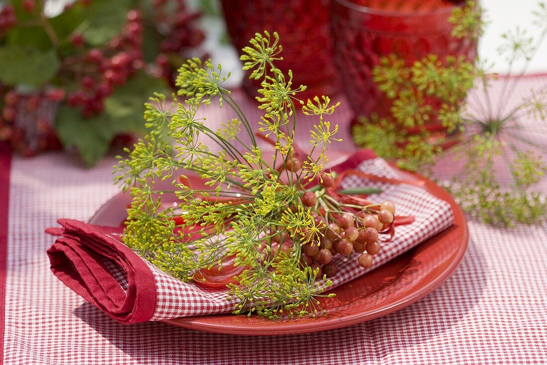 Place-setting with guelder rose berries and dill flowers