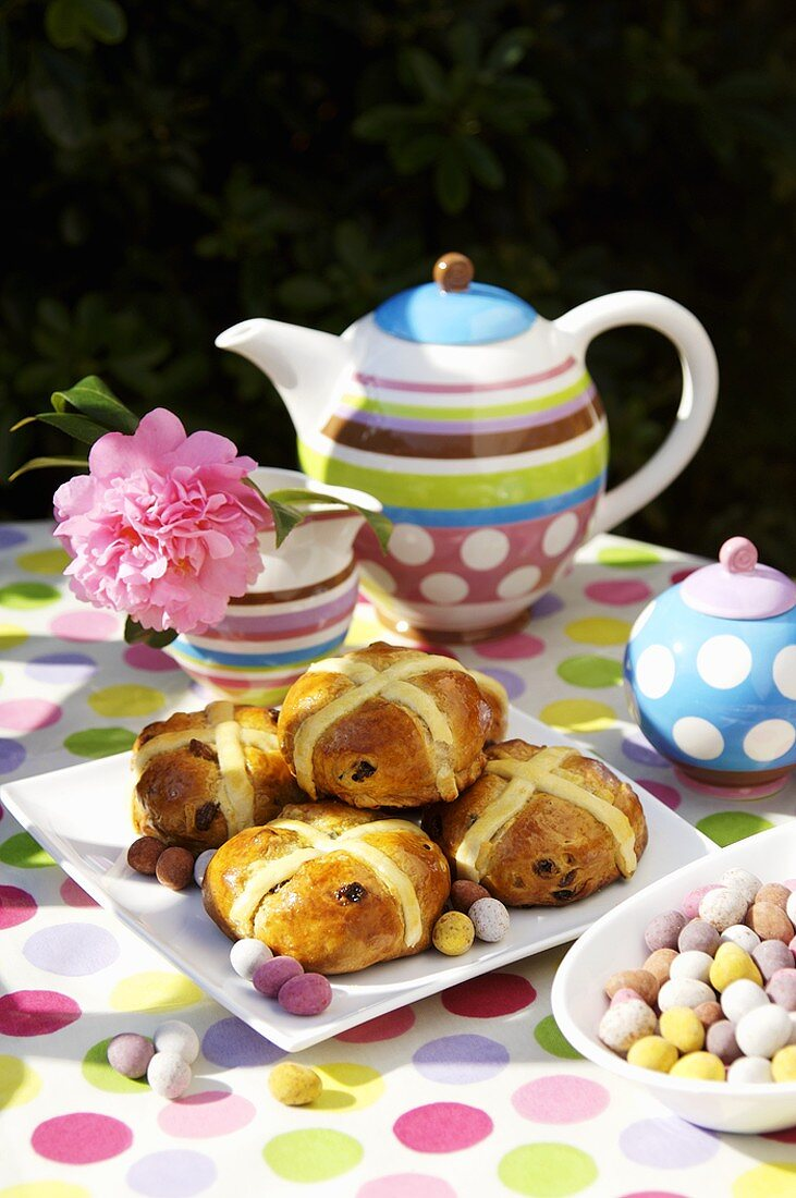 Hot cross buns & coloured Easter eggs on table laid for coffee