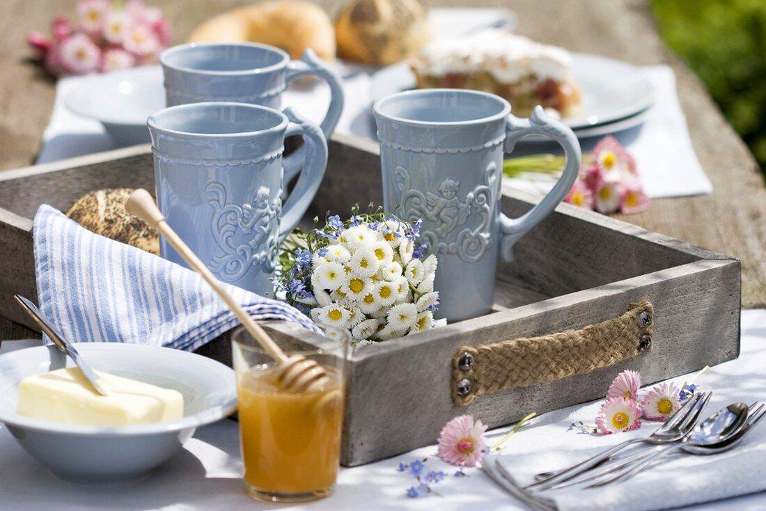 Mugs & posy of bellis flowers on tray, oilseed rape honey