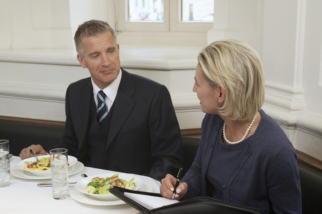 Businessman speaking to secretary over meal in restaurant