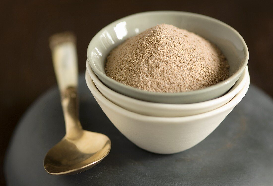 Cocoa powder in a small bowl on a pile of bowls