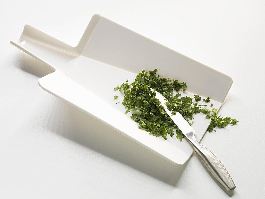 Chopped herbs on a flexible chopping board