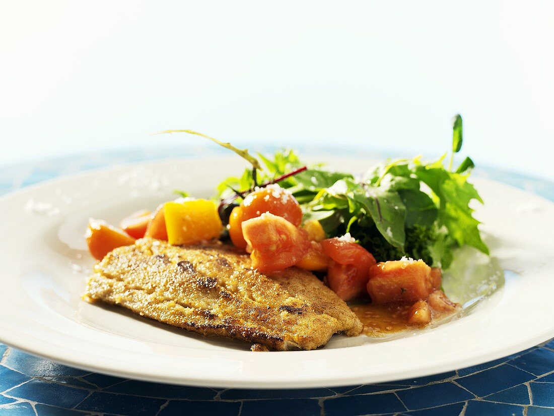 Fried salmon fillet with mustard crust and tomato salad