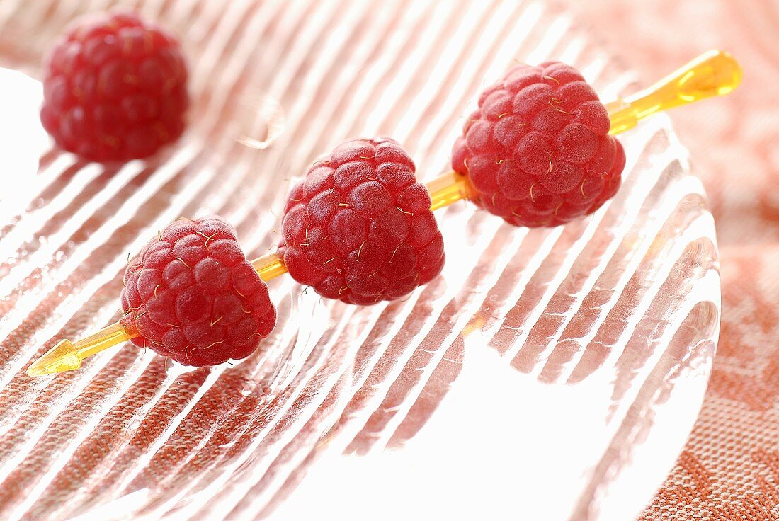 Raspberries on cocktail stick on glass plate
