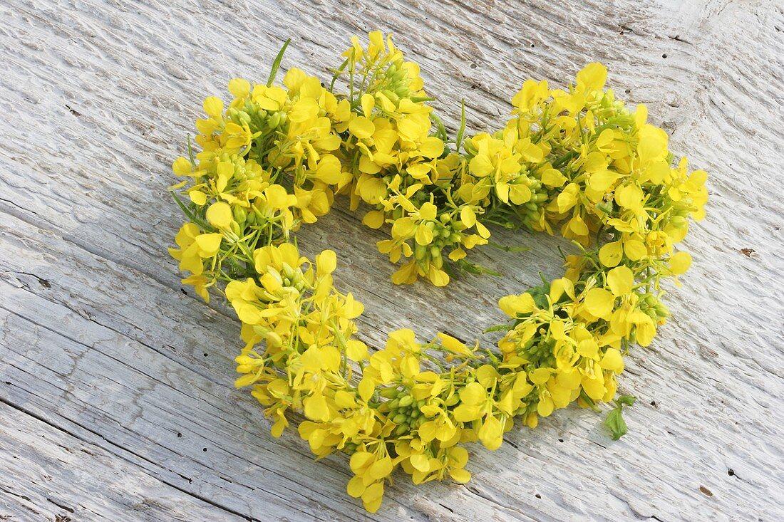 Small heart-shaped wreath of oilseed rape flowers