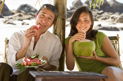 Father eating watermelon, daughter drinking coconut milk on beach