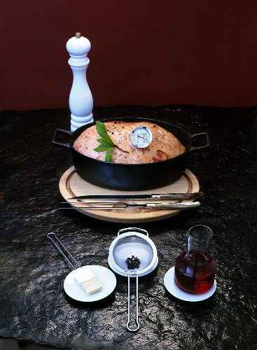Joint of pork in roasting dish with meat thermometer & ingredients