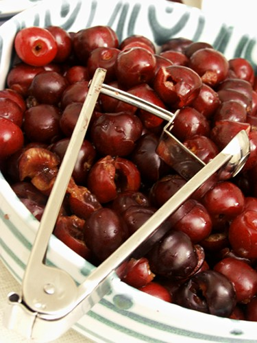 Cherry Pitter Resting on a Bowl of Pitted Cherries