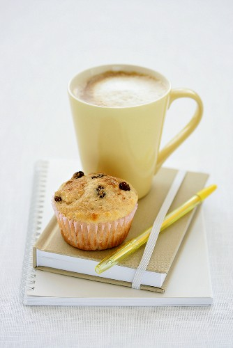 A raisin muffin with a cafe au lait