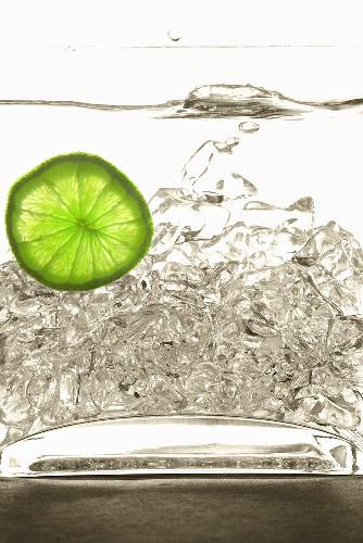 Eis fällt in Wasser mit Limettenscheibe