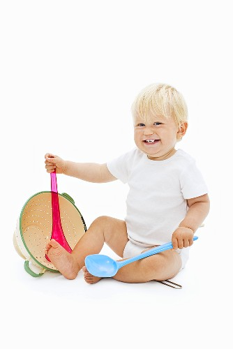 Little child playing with kitchen utensils