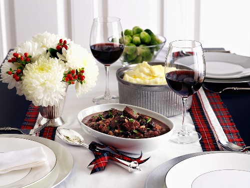 Saddle of venison, mashed potatoes and Brussels sprouts on a table decorated for Christmas
