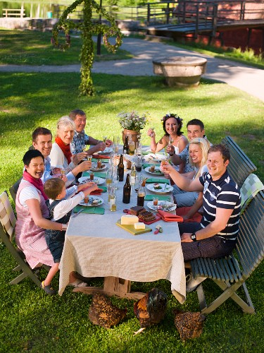 People eating in a garden (mid-summer party, Sweden)