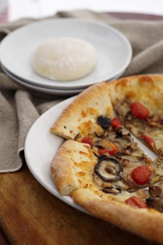 Wild Mushroom and Tomato Pizza; Sliced on a White Plate; Pizza Dough