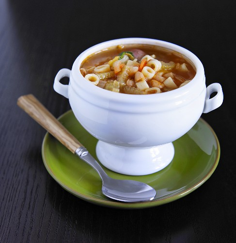Bowl of Minestrone Soup on a Green Plate with Spoon