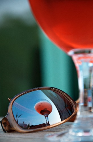 An aperitif in a glass reflected in a pair of sunglasses