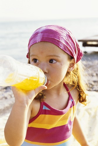 Girl on beach drinking out of a plastic bottle