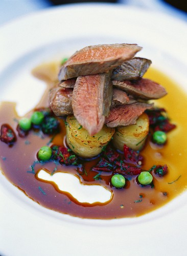 Lamb fillets on potatoes in beetroot sauce with peas