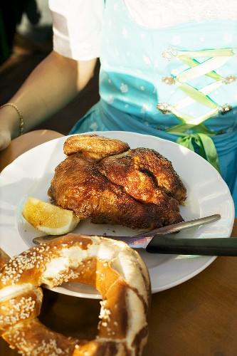 Half a roast chicken with a soft pretzel in a beer garden
