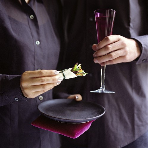 Hands with mini-wrap and a glass of champagne