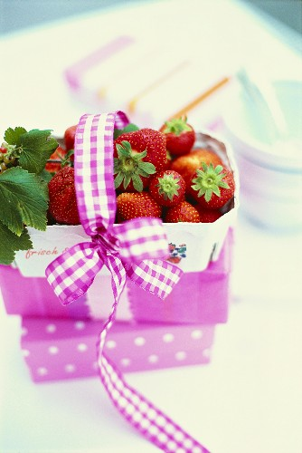 Purple basket of fresh strawberries with bow