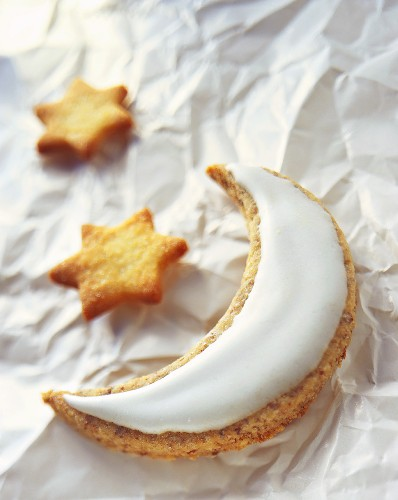 Moon biscuit with glacé icing and star biscuits on paper