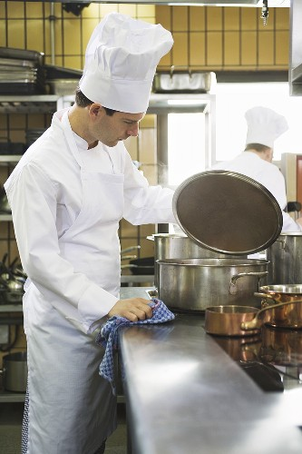 Chef checking the contents of a pan