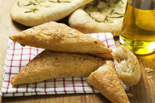 Triangular puff pastry pasties, focaccia and olive oil