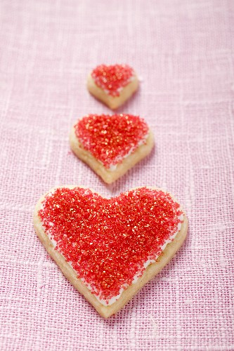 Three heart-shaped biscuits with red sugar