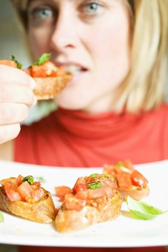 Frau isst Bruschetta mit frischem Basilikum