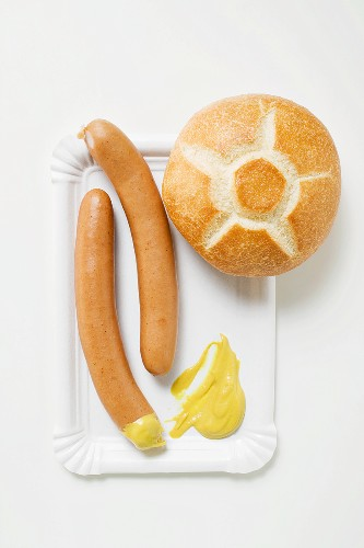 Frankfurters, bread roll and mustard on paper plate