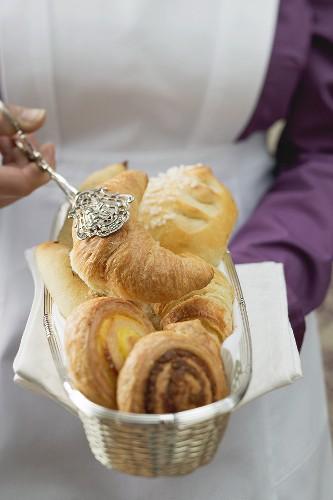 Chambermaid serving breakfast pastries from bread basket