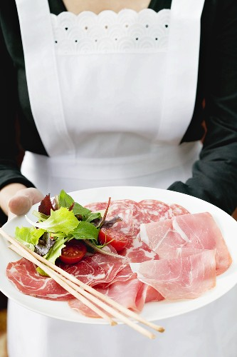 Waitress serving Italian sausage platter with grissini