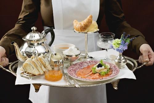 Chambermaid serving luxury breakfast tray