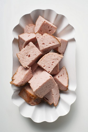 Pieces of Leberkäse (a type of meatloaf) in paper dish