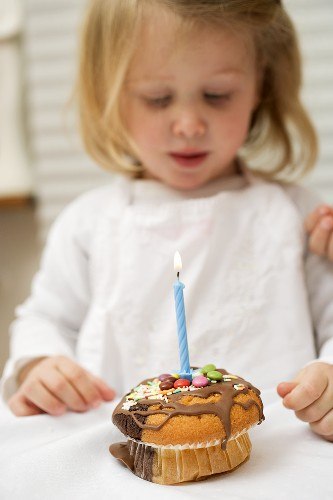 Small girl looking at muffin with one burning candle
