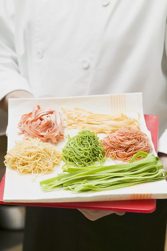 Chef presenting various types of home-made pasta