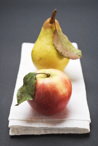 Red apple and pear with leaves on cloth