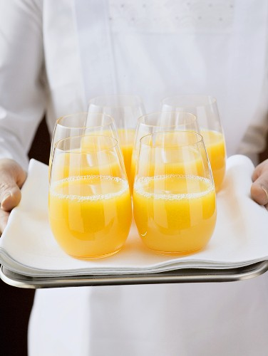 Chambermaid serving several glasses of orange juice on tray