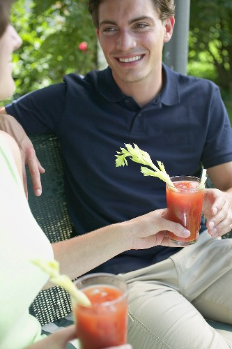 Woman handing tomato drink to young man