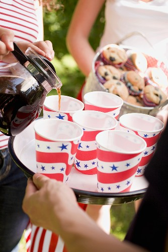 Woman pouring coffee into paper cups (4th of July, USA)