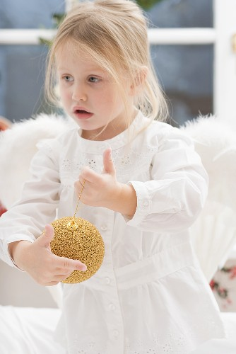 Small girl with angel's wings holding Christmas bauble