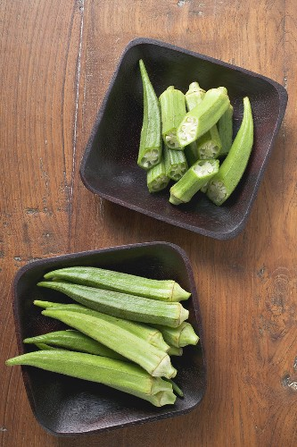 Several okra pods, whole & cut in two, in two dishes