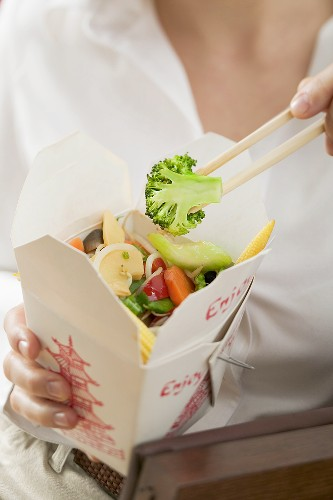 Woman eating Asian vegetable dish out of take-away container