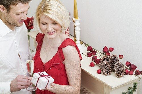 Man giving Christmas gift to woman by fireplace
