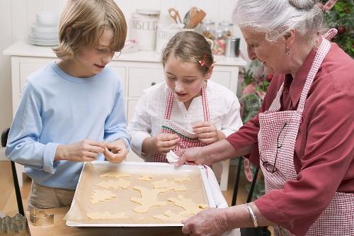 Grandmother showing grandchildren baking tray of Xmas biscuits
