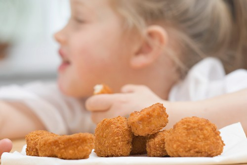 Little girl eating chicken nuggets – License Images – 969912 ❘ StockFood