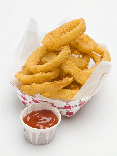 Deep-fried onion rings in paper dish, ketchup beside it