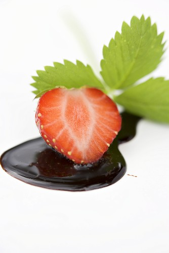 Half a strawberry with chocolate sauce and strawberry leaf