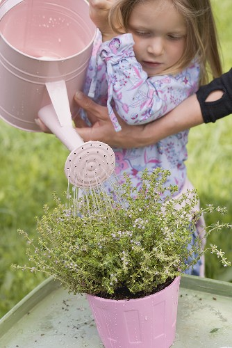 Mother helping daughter to water thyme